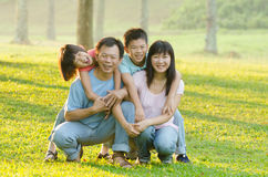 Family lying outdoors being playful and smiling Royalty Free Stock Photos