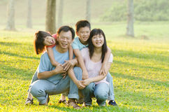 Family lying outdoors being playful and smiling Stock Photography