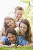 Family lying outdoors smiling Stock Image