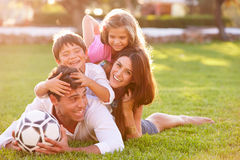 Family Lying In Pile Up On Grass Together Stock Photo