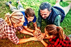 Family lying and putting their hands together in park. Playful family lying and putting their hands together in park royalty free stock photography