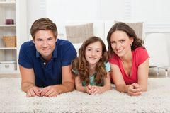 Family lying on rug at home Royalty Free Stock Photos
