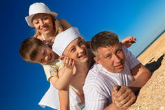 Family lying on sand Stock Photos