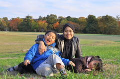A family lying and sitting on grass during autumn. The portrait of a mother bonding with her son and daughter by the site of trees in fall season Stock Photo