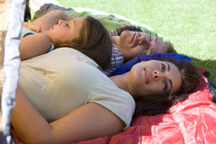 Family lying on sleeping bags in tent entrance on garden lawn, father and children (7-9) sleeping, mother daydreaming, side view stock photo