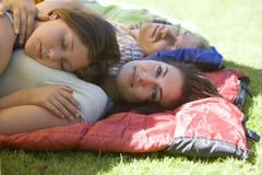 Family lying on sleeping bags in tent entrance on garden lawn, girl (7-9) sleeping on mother�s chest, woman smiling, side view, royalty free stock images