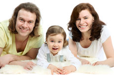 Family are lying on white fluffy fur royalty free stock image