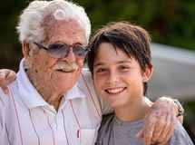 Multi-generational family in his home`s garden stock photography