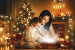 Family with magic gift box. Merry Christmas and Happy Holiday! Loving family mother and child with magic gift box stock photos
