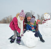 Family make a snowman. Happy beautiful children with father building snowman outside in winter time Stock Images