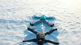 A family makes a figure of a snow angel in a clearing in the forest. Aerial photography of a girl and a boy lying on the stock footage