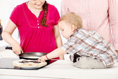 Family makes pancakes in the kitchen. Happy family makes pancakes in the kitchen Stock Images