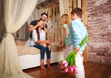 Family makes  surprise mother giving presents of flowers. Family children makes a surprise mother giving presents a bouquet of flowers Stock Images