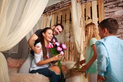 Family makes  surprise mother giving presents of flowers. Family children makes a surprise mother giving presents a bouquet of flowers Stock Photography