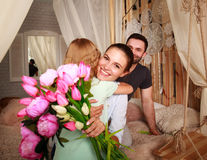 Family makes surprise mother giving presents of flowers. Family children makes a surprise mother giving presents a bouquet of flowers Royalty Free Stock Photos
