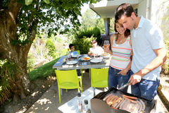 Family making barbecue at home garden Stock Image