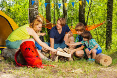 Family making camp fire with fireplace log pieces Royalty Free Stock Images