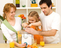 Family making fresh fruit juice together Royalty Free Stock Photo