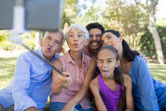 Family making funny faces while taking a selfie in the park. Playful family making funny faces while taking a selfie in the park Stock Photo