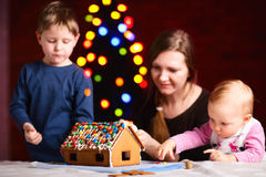 Family making gingerbread house Royalty Free Stock Photography