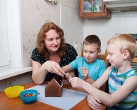 Family making gingerbread house Stock Image