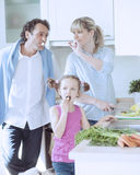 Family making a healthy salad in the kitchen Stock Photo