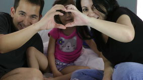 Family making heart symbol from hands to their girl stock footage