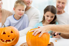 Family making lantern of pumpkins for helloween Royalty Free Stock Photo