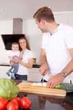 Family Making Meal. A family at home in the kitchen making a meal together, shallow depth of field, critical focus on father Royalty Free Stock Images