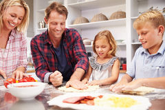 Family making pizza together Royalty Free Stock Photos