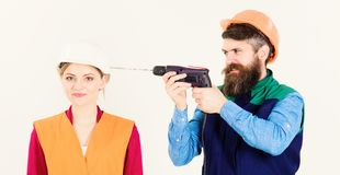 Family making repair. Get nerves concept. Man with smiling face. Drills head of woman, white background. Woman with smiling face in helmet, hard hat. Builder royalty free stock photography
