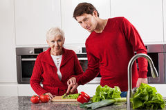 Family making salad together. Elderly lady cutting vegetables with her grandson for salad Stock Image