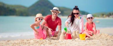 Family making sand castle at tropical beach. Family of four making sand castle at tropical white beach stock photo