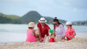 Parents with kids play making sand castle at tropical white beach. Family making sand castle at tropical beach stock video