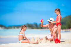Family making sand castle at tropical white beach. Father and two girls playing with sand on tropical beach Stock Images