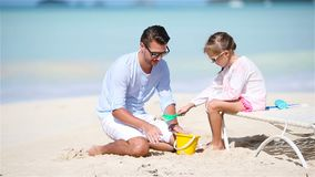 Father and little adorable girl making sand castle at tropical beach. Family making sand castle at tropical white beach stock footage