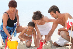 Family making sandcastle Stock Images