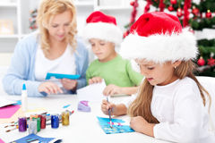 Family making seasonal greeting cards together Stock Photos