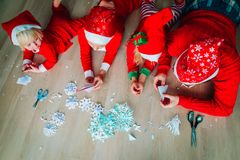 Family making snowflakes from paper, Christmas crafts. Father and kids making snowflakes from paper, Christmas crafts, prepare for family Christmas celebration royalty free stock photos