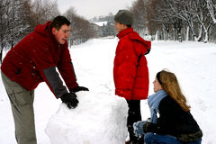 Family Making Snowman. Man and two children making snowman when snowing Stock Photography
