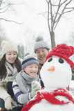 Family Making Snowman In A Park In Winter Stock Image