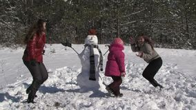 Family making a snowman together. The dance around the snowman in the woods stock footage