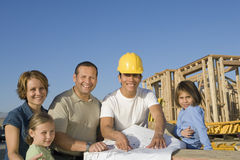 Family And Male Architect With Blueprint. Portrait of happy family and male architect with blueprint at construction site Stock Photo