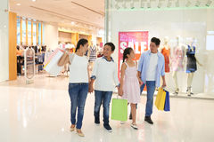 Family in mall. Cheerful Vietnamese family walking in shopping mall Royalty Free Stock Photo