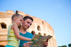 Family with map in front of Colosseum. Father and girl searching the attraction background the famous area in Rome Stock Photo