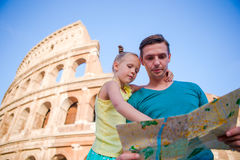 Family with map in front of Colosseum. Father and girl searching the attraction background the famous area in Rome Royalty Free Stock Photo