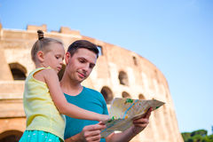 Family with map in front of Colosseum. Father and girl searching the attraction background the famous area in Rome Royalty Free Stock Photography