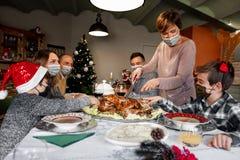 Family in masks celebrating over Christmas during Corona virus Pandemic