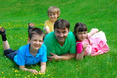 Family in the meadow. Three children and their uncle/father lie down in a meadow, posing happily Stock Photo