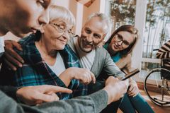 Family. Meeting. Together. Nursing. Older People. Sear and Yellow Leaf. Something on Tablet. Happy. Leptop. Senior Couple. Young People. Visit. Old People Play stock images